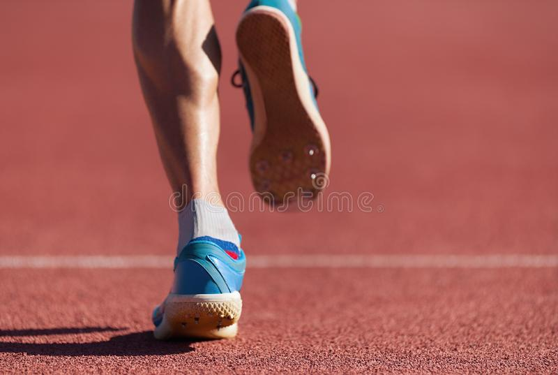 Man runner running on track. Close-up on running shoes royalty free stock images