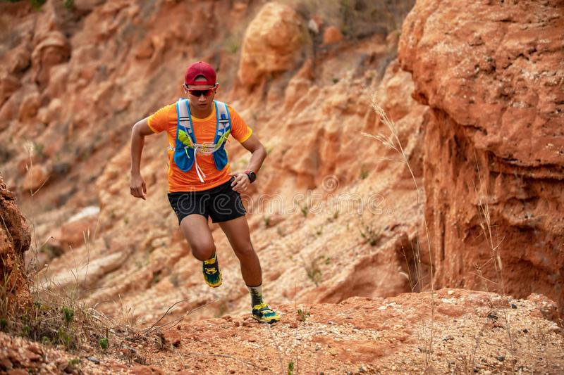 A man Runner of Trail . and athlete`s feet wearing sports shoes for trail running in the mountains royalty free stock image