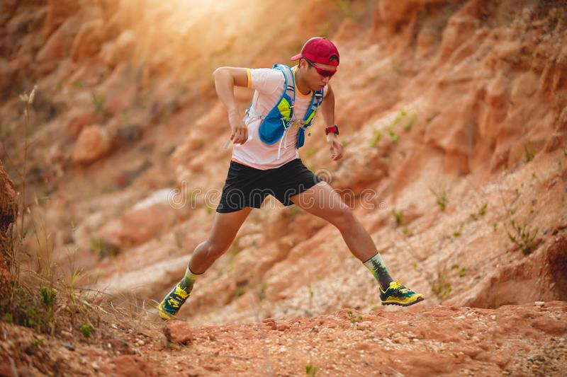A man Runner of Trail . and athlete`s feet wearing sports shoes for trail running in the mountains.  royalty free stock photos