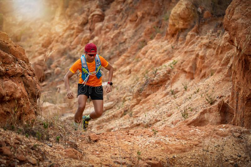 A man Runner of Trail and athlete`s feet wearing sports shoes for trail running in the forest.  stock photography
