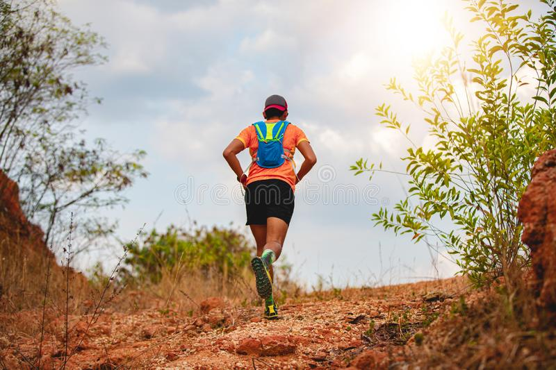 A man Runner of Trail . and athlete`s feet wearing sports shoes for trail running in the mountains stock image