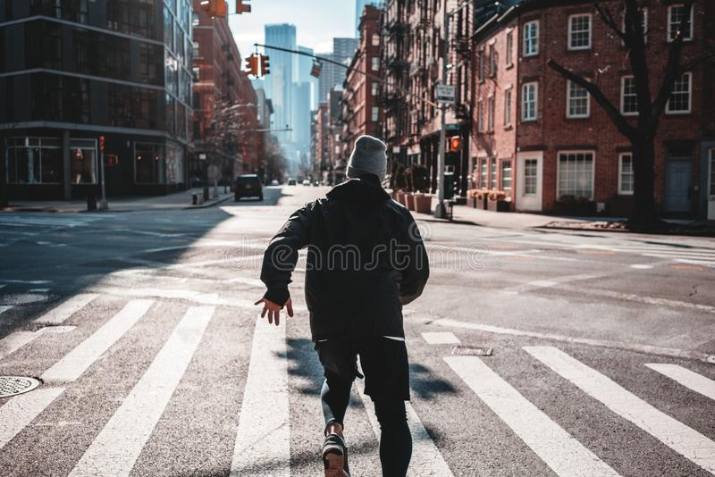 Back view on male athlete while run through New-Yrok streets royalty free stock image