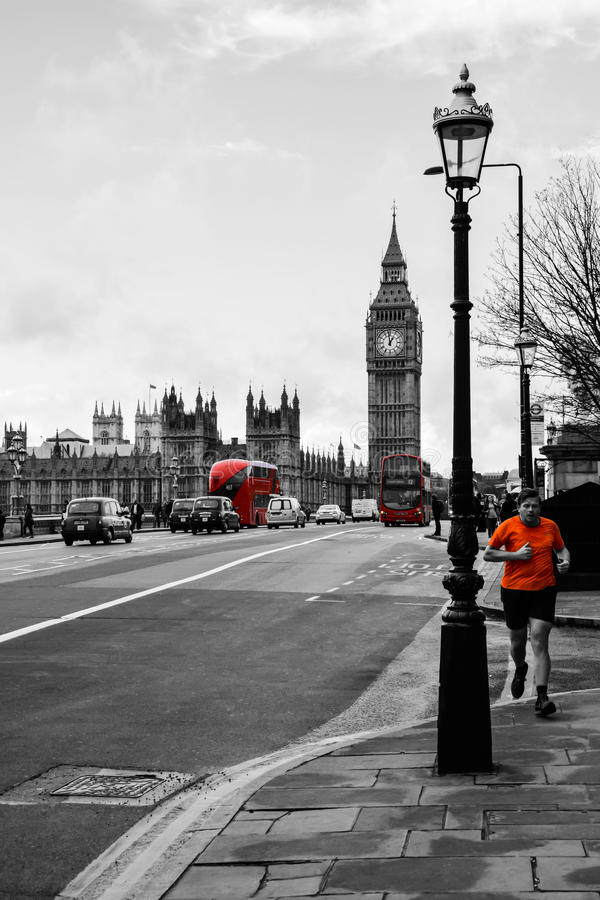 Man running across bridge. A picture of a man running across Westminster Bridge with the iconic Big Ben clock in the background. A great picture to demonstrate royalty free stock photo