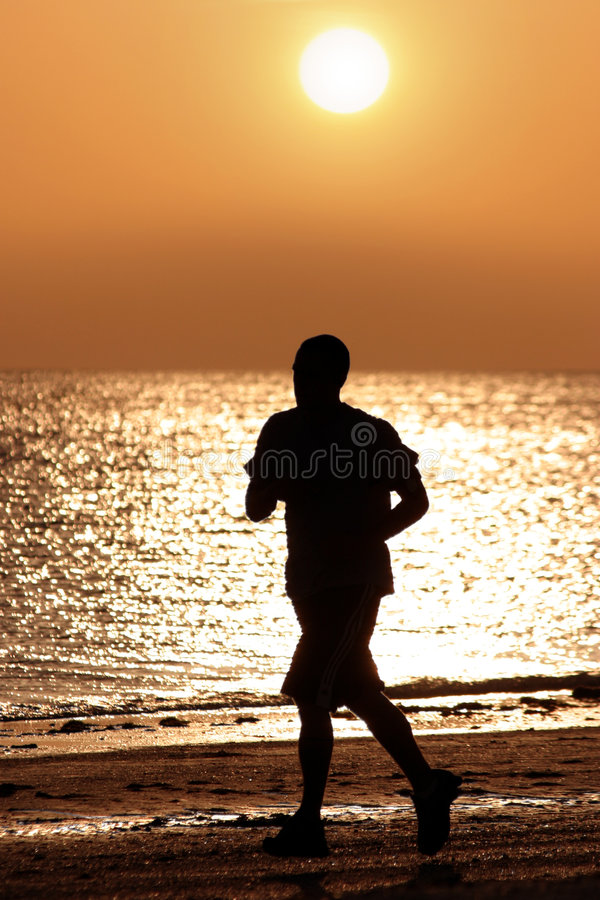 Man running on the beach royalty free stock photo