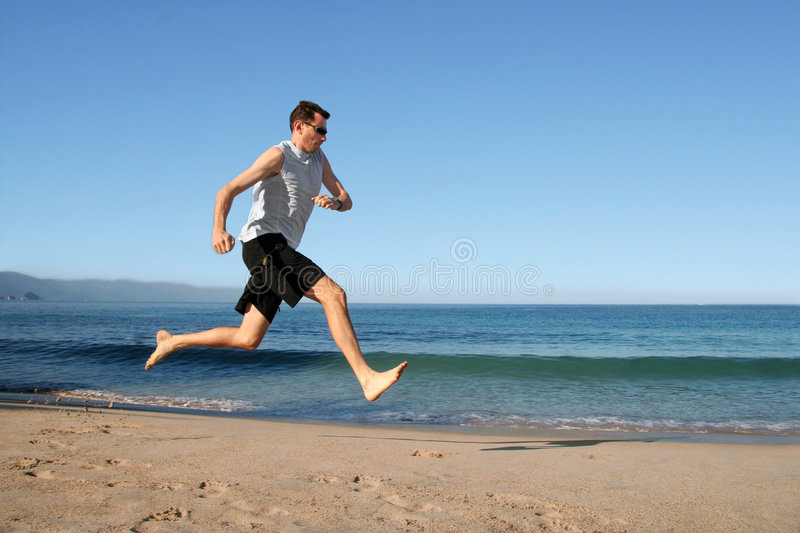 Man running on the beach royalty free stock photography