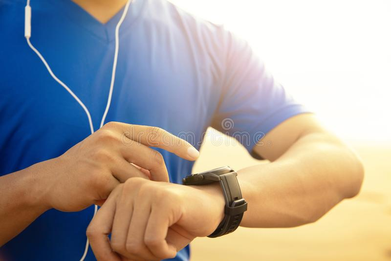 Man running on beach and checking Heart Rate Monitor On watch. Young Man running on beach and checking Heart Rate Monitor On watch royalty free stock image