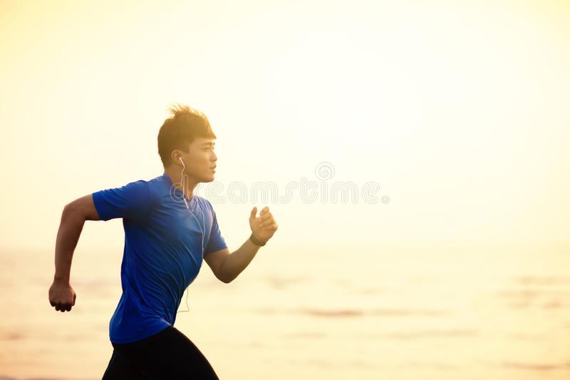 Man running on  beach at sunset. Young Man running on  beach at sunset royalty free stock image