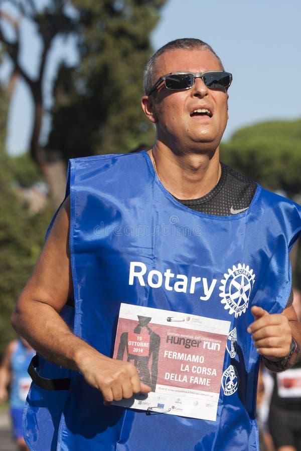 Man running, bib rotary (Hunger Run 2014, FAO/WFP) royalty free stock photo