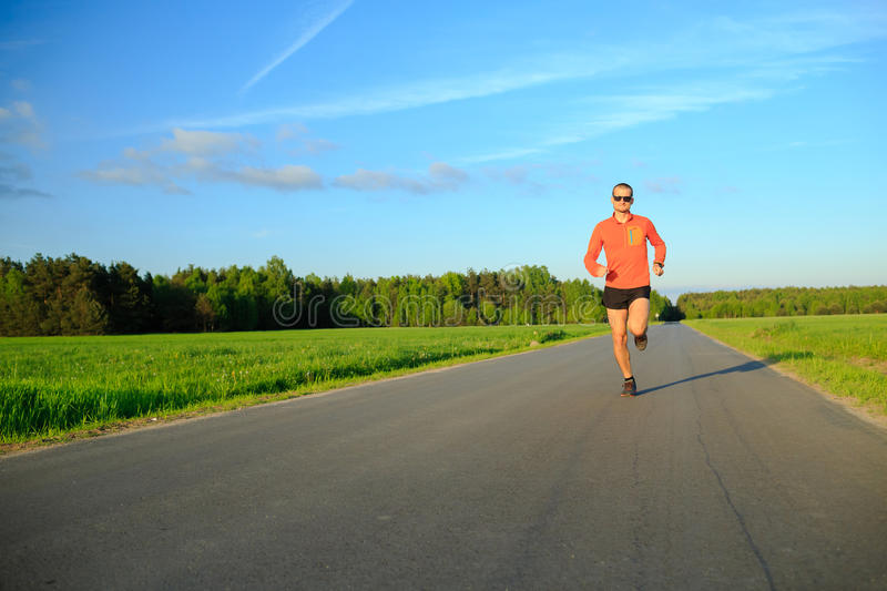 Man running on country road, training inspiration and motivation. Man runner running on country road, training inspiration and motivation in summer sunset. Young royalty free stock images
