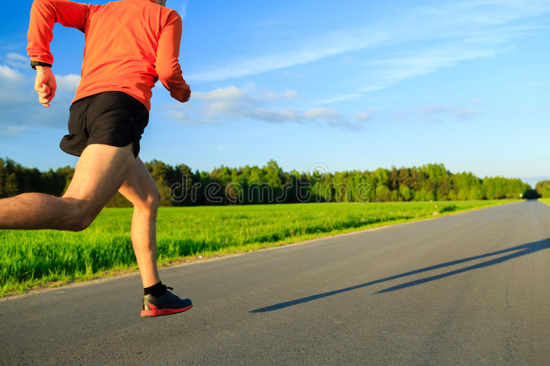 Man running on country road, training inspiration and motivation. Man runner running on country road, training inspiration and motivation in summer sunset. Young stock photo