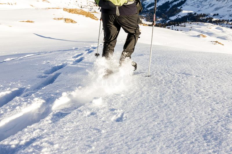 Man running downhill through deep snow with snoeshoes and hiking sticks. royalty free stock photos