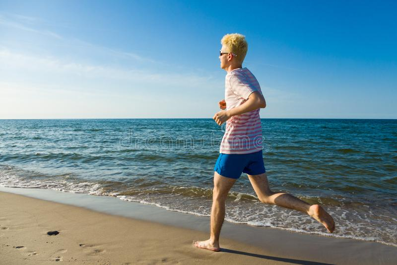 Man running, jumping on beach. Young man running, jumping on beach royalty free stock photos