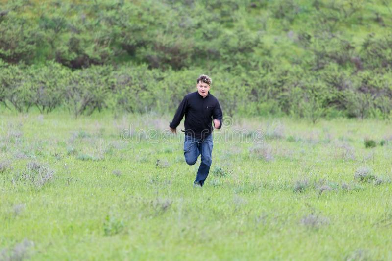 Man running in a meadow stock photo