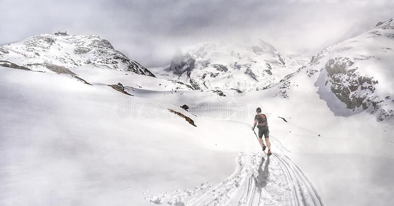 Man running through the mountains ascending towards the refuge stock images