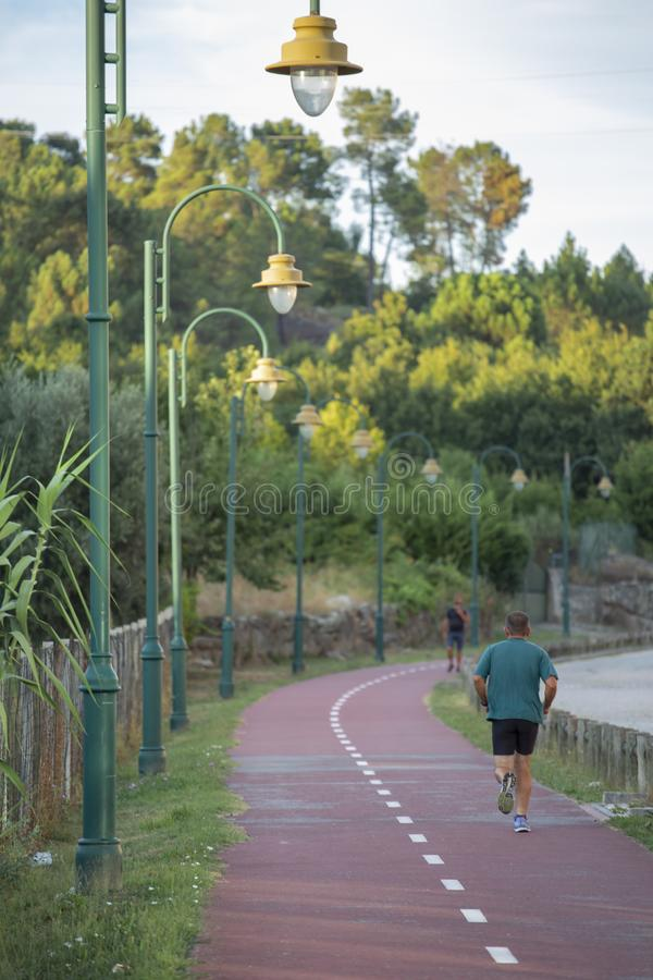 Man running on pedestrian cycle path, in Viseu, Portugal. Man cycling on pedestrian cycle path, with street lamps, blue sky as background and vegetation, in stock images