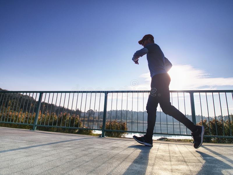 Man is running quickly on the shore bridge. Silhouette of active man stock images