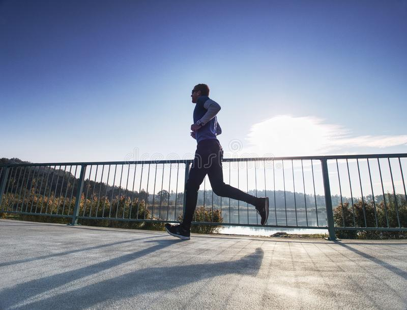 Man is running quickly on the shore bridge. Silhouette of active man royalty free stock photos