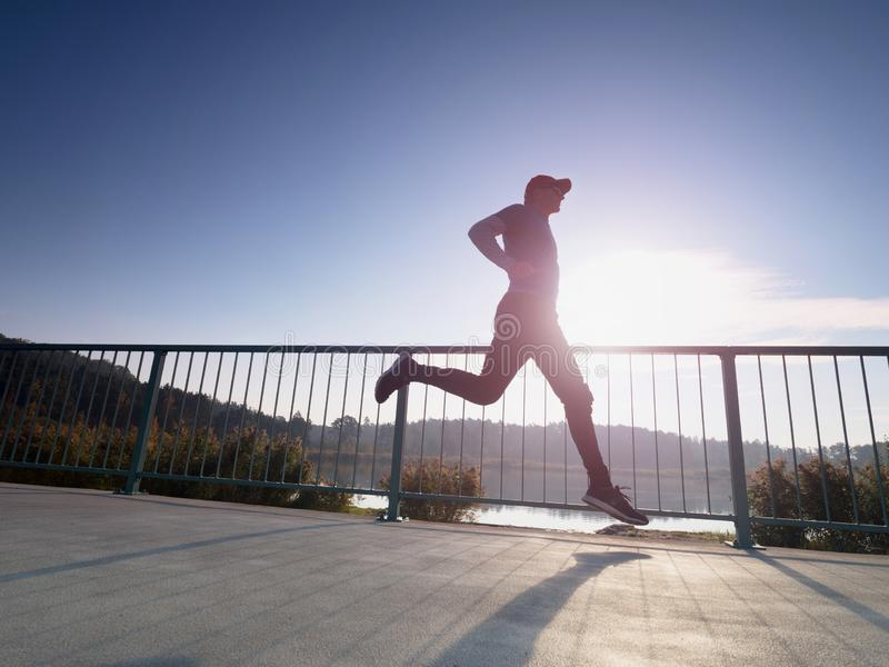 Man is running quickly on the shore bridge. Silhouette of active man stock image