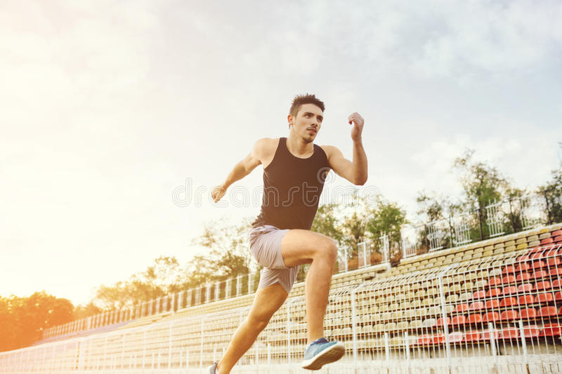 Man running on a racing track. Athletic man running on a racing track royalty free stock photos