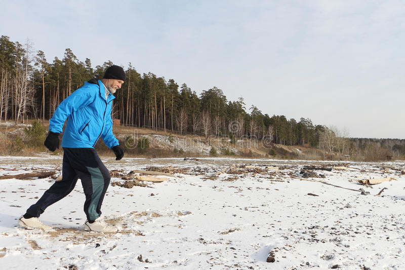 The man running on snow on the river bank. The man in a blue jacket running on snow on the river bank stock image