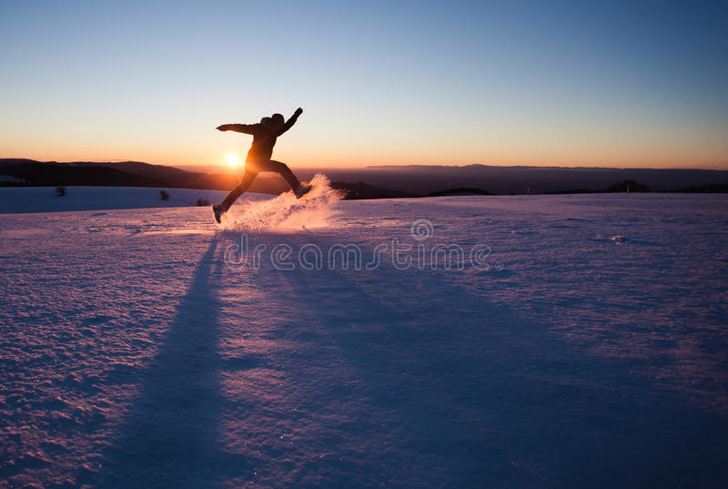 Man running through snow in winter landscape. Silhouetted man running through snow in winter landscape stock images