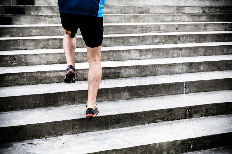 Man running on stairs, sports training. Man runner running on stairs in city, sport training. Young male athlete training and doing workout outdoors in city royalty free stock photography