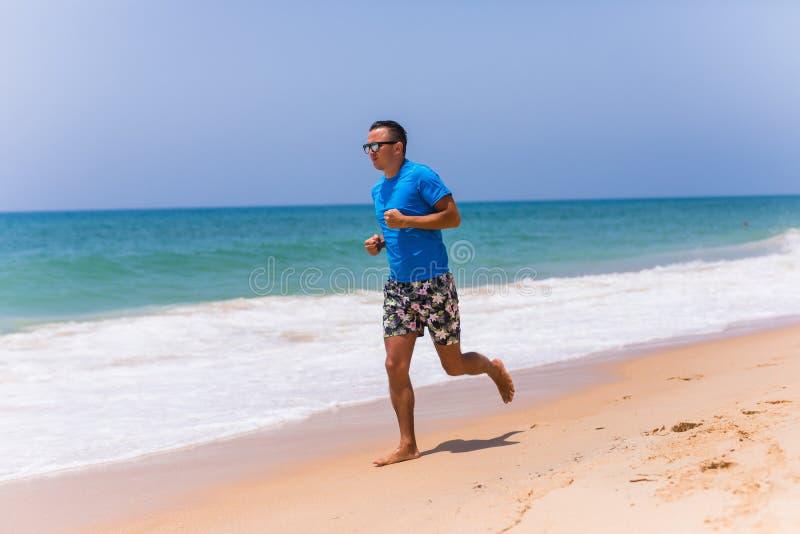 Man running on sunny beach near ocean royalty free stock photography