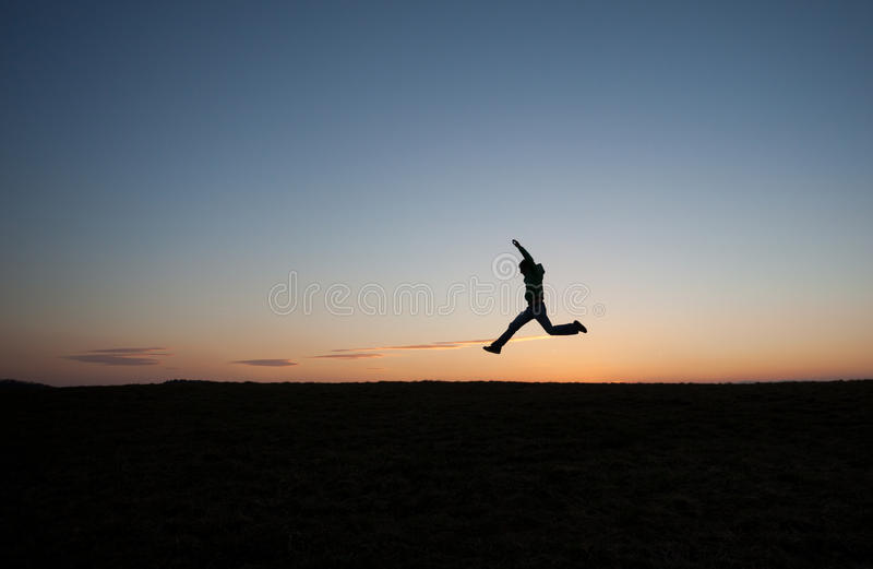 Man running in sunset sky on hill. Silhouette of man running in sunset sky on hill stock images