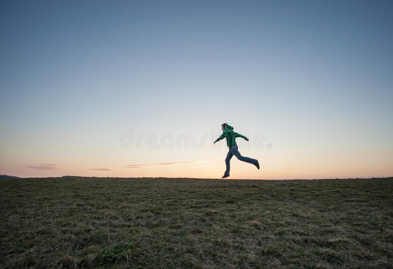 Man running in sunset sky on hill. Silhouette of man running in sunset sky on hill stock photos