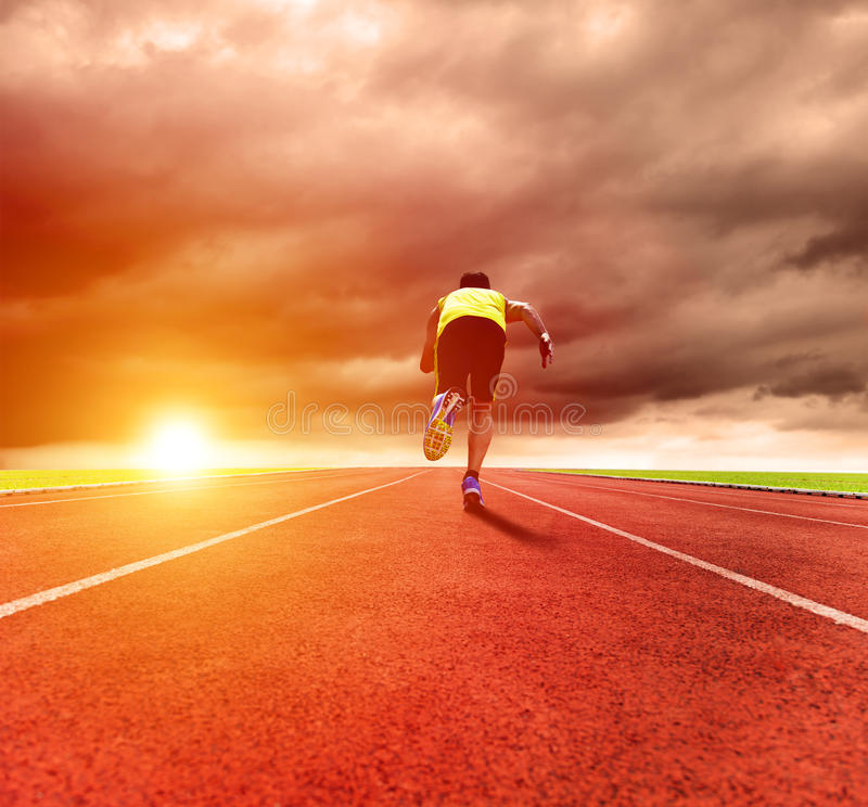Man running on the track with sunrise background. Young man running on the track with sunrise background stock photo