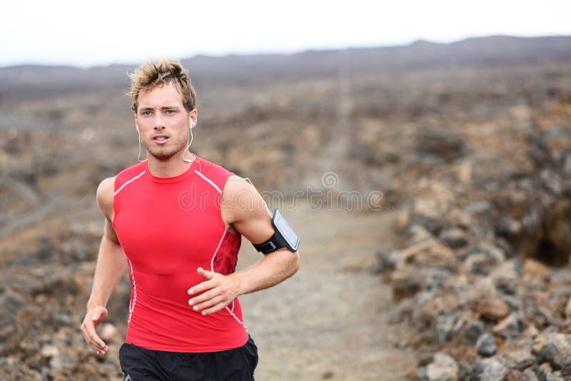 Man running - trail runner training. Man running - trail runner cross country training outdoors for marathon or triathlon ironman. Handsome male athlete working stock images