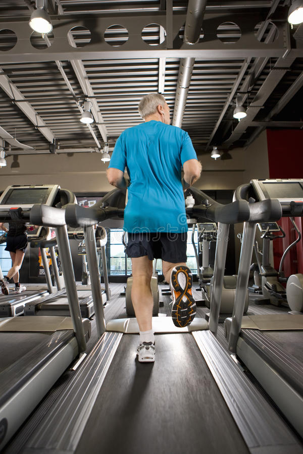 Man running on treadmill in health club stock images