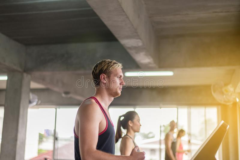 Man running on treadmills doing cardio training in a gym,Healthy lifestyle concept royalty free stock image