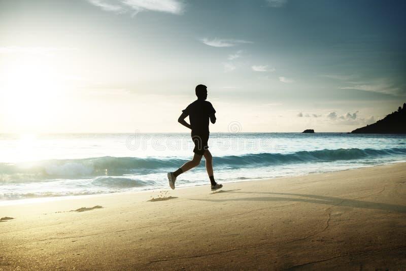 Man running on tropical beach royalty free stock photos