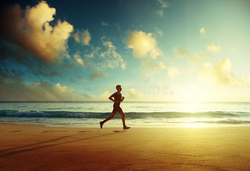 Man running on tropical beach at sunset stock images
