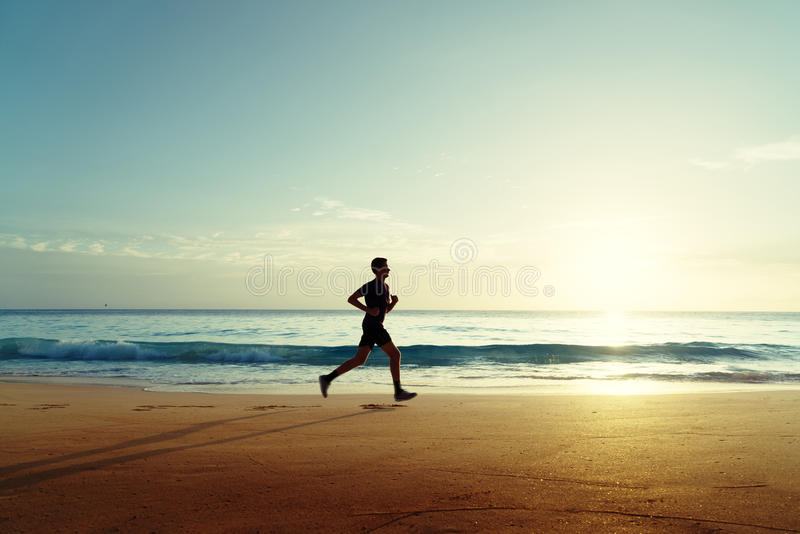 Man running on tropical beach at sunset royalty free stock photos