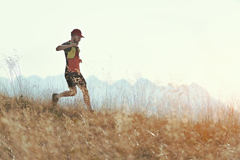 Man runs downhill among the autumn mountain meadows royalty free stock images