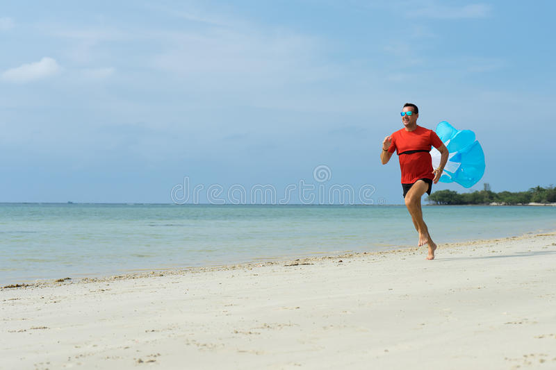 The man runs, runs on the beach, in the tropical country plays sports, with attached running a parachute behind. The man runs, runs on the beach, in the stock images