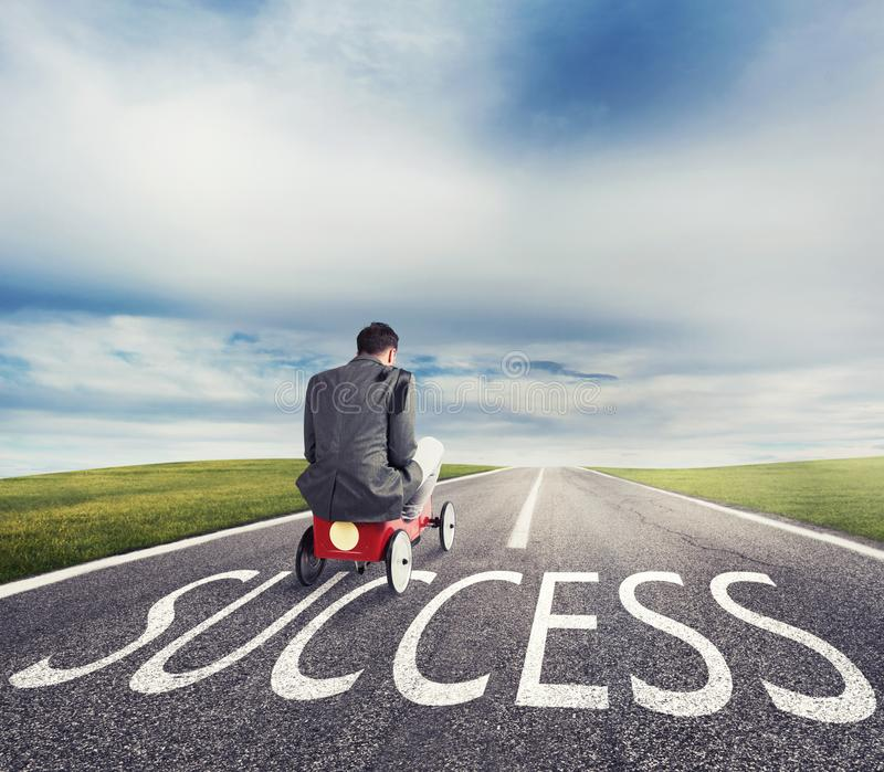 Man runs with a toy car on success way. Concept of successful businessman and company startup stock image