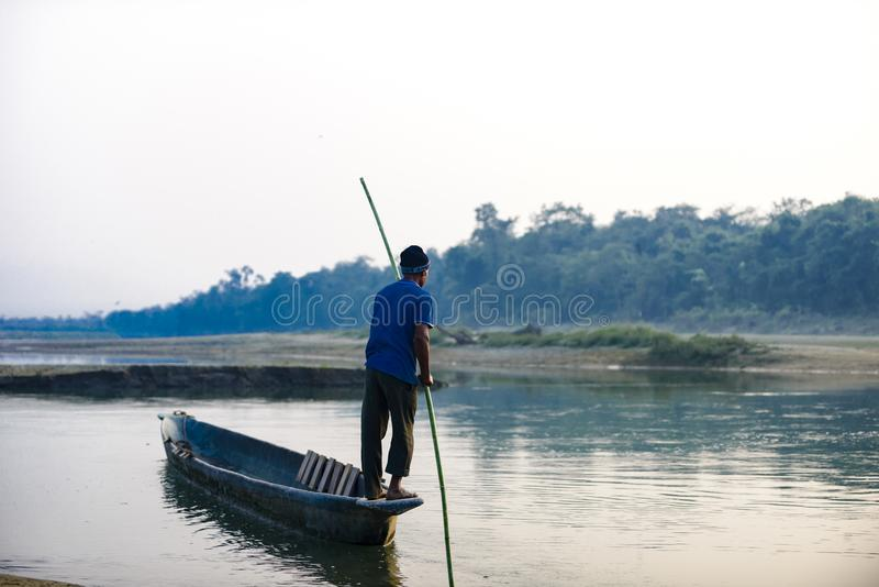Man runs a wooden boat on the river, Nepal, Chitwan National Park, December stock image