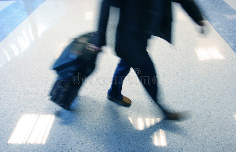 Man rushing in ariport to catch his flight stock image
