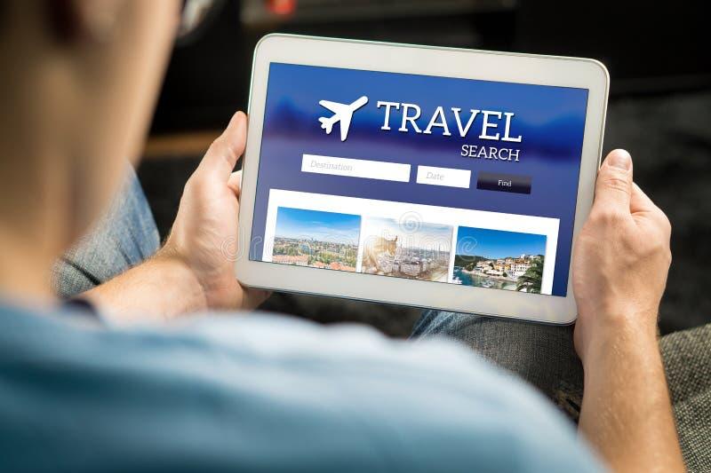Man sökande av billiga flyg, av hotellet eller av feriepacken direktanslutet fotografering för bildbyråer