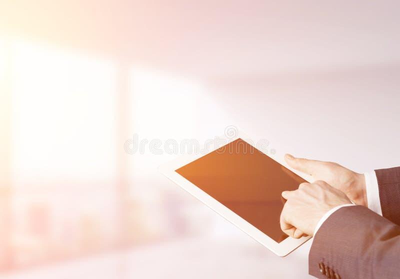 Man& x27; s手与片剂屏幕一起使用在被日光照射了办公室 免版税图库摄影