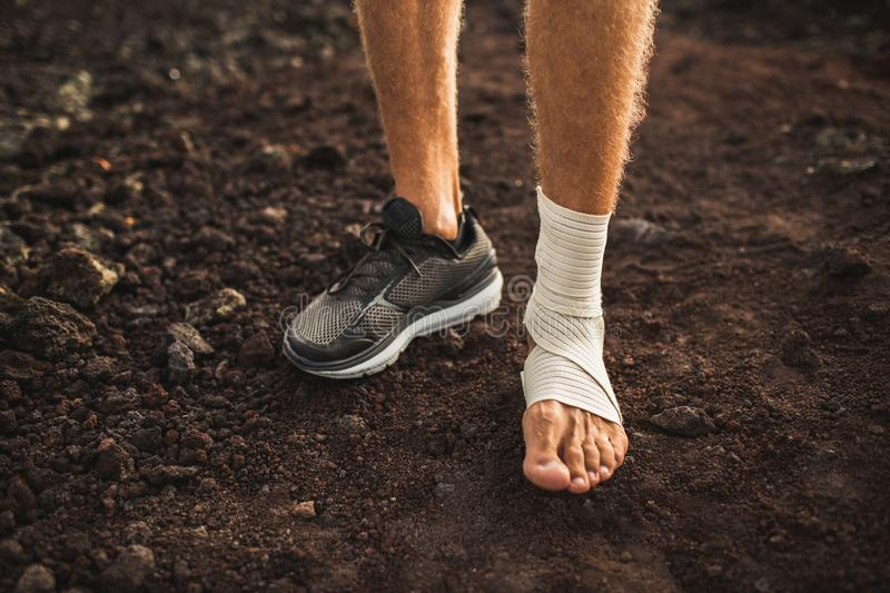 Man`s ankle in compression bandage. Leg injury. While trail running outdoors. First aid for sprained ligament or tendon royalty free stock photos