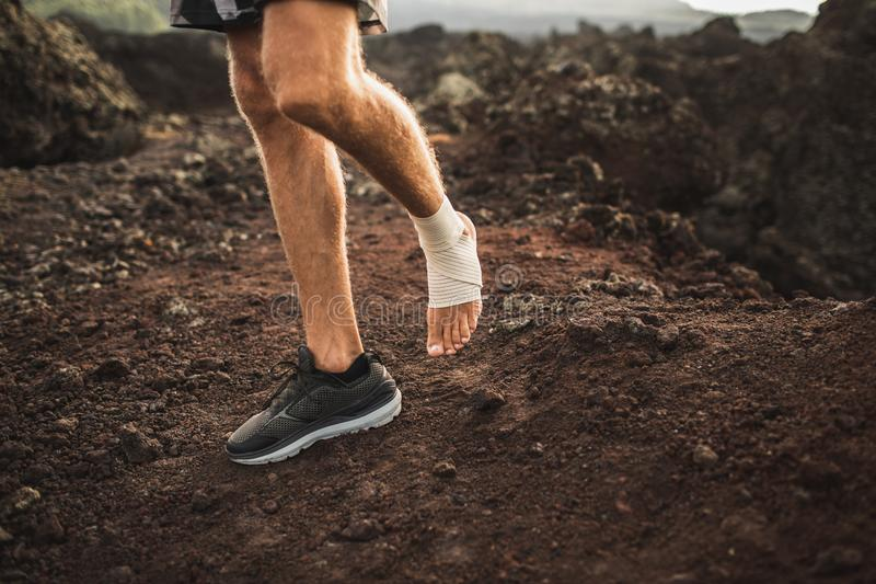 Man`s ankle in compression bandage. Leg injury. While trail running outdoors. First aid for sprained ligament or tendon stock image