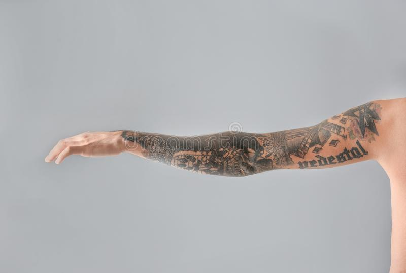 Man`s arm with stylish tattoos. On grey background royalty free stock images