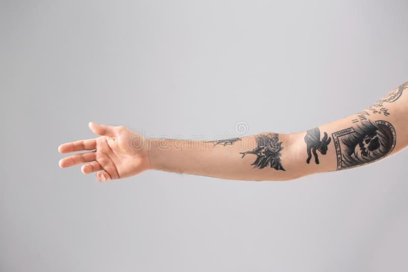 Man`s arm with stylish tattoos. On grey background stock photo