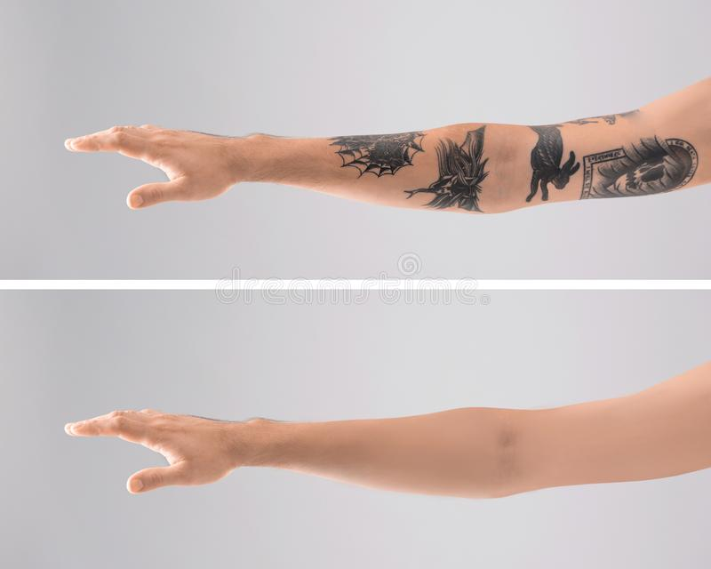 Man`s arm with stylish tattoos. On grey background stock photography