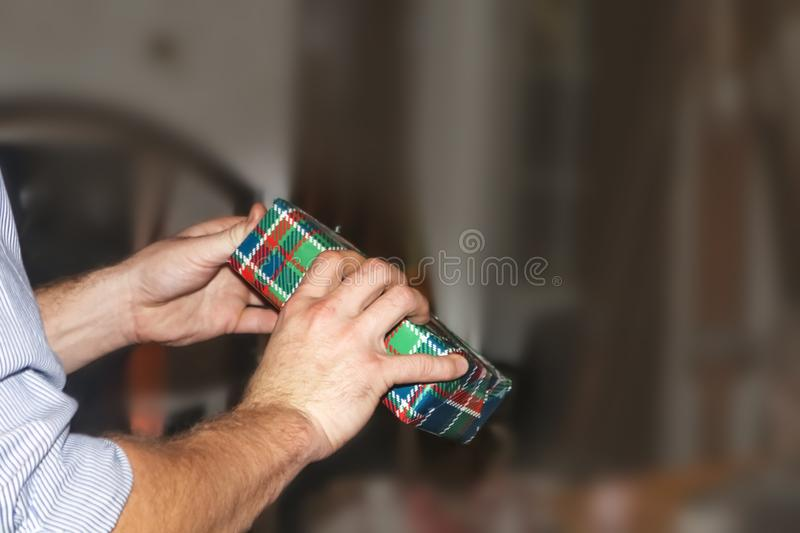 Man`s arms and hands opening plaid wrapped Christmas present against very blurred background - room for text royalty free stock images