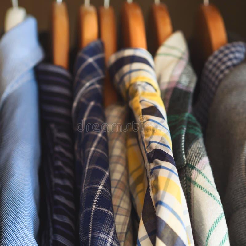 Man`s closet hangers shirts closeup. Man`s closet. Hangers with shirts closeup. Male wardrobe royalty free stock photos